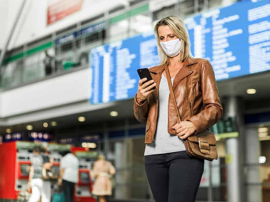 Frau plant am Bahnhof ihre Reise mit den Öffis per App.